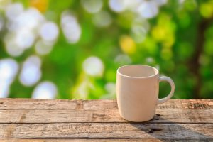White coffee cup on wooden table at morning sunlight and green bokeh background